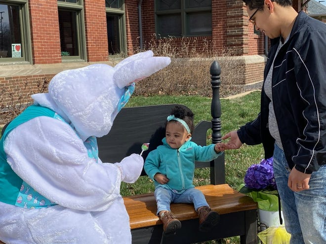 """One and a half year old Khalia Lovin-Nunn is unsure of the Easter bunny and gets support from her mom Jazzie. Logan County Tourism kicked off the """"Hop Around Downtown"""" program that features downtown merchants offering coupons and discounts to shoppers."""