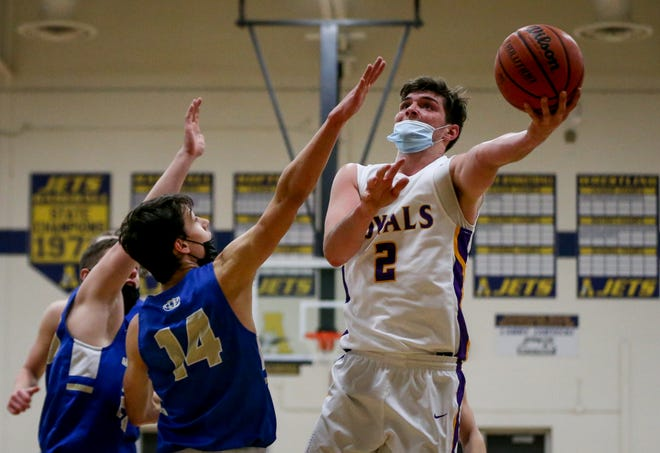 Blissfield's Ty Wyman scores against Ryan Gennoe (14) and Shea Peare of Jefferson in the finals of the Division 2 District at Airport Saturday night. Blissfield won 92-42.