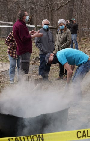 """Patrick Malone of Wantage, tends the fire in the """"maple arch"""" fireplace as another volunteer explains the traditional method of making maple syrup on Saturday, March 27, 2021 at historic Lusscroft Farm in Wantage."""