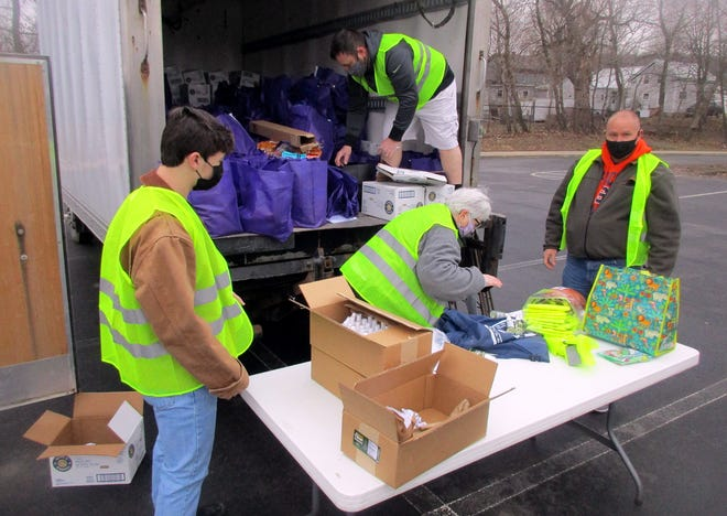 Route 20 Catholic volunteers, front from left, Austin Zaleski, Lynne Pletl and Joe Sternburg and, in truck, Chris Doroshenko prepare bags of food March 27 during the church group's food giveaway at Madison Central School in Madison.