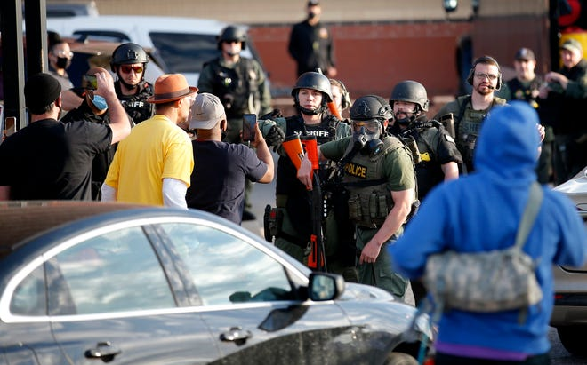 Protesters argue with police outside the Oklahoma County jail last month after a corrections officer was taken hostage and police shot to death an inmate, ending the incident.