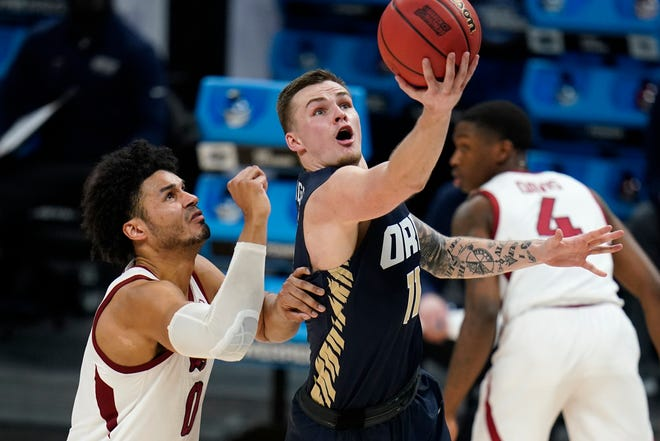 Oral Roberts' Carlos Jurgens (11) drives to the basket ahead of Arkansas' Justin Smith during the second half of a Sweet 16 game Saturday night in Indianapolis.