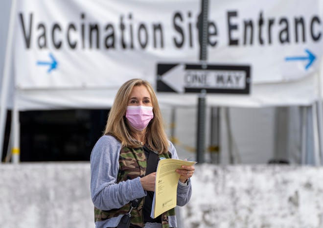 Jodi Greene, 50, walks to her car after receiving the Pfizer COVID-19 vaccine at the South Florida Fairgrounds last week. GREG LOVETT / THE PALM BEACH POST
