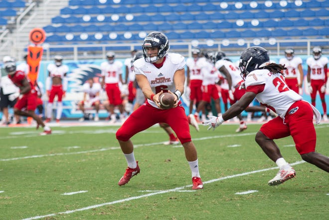 Nick Tronti, handing the ball off during Saturday's scrimmage, earned the praise of FAU coach Willie Taggart.