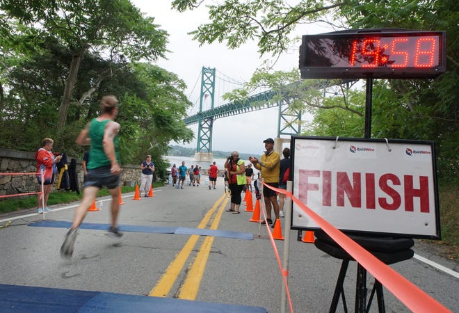 Runners cross the finish line at the base of Old Ferry Road in Bristol during the Mount Hope Bridge 5K race in 2018.