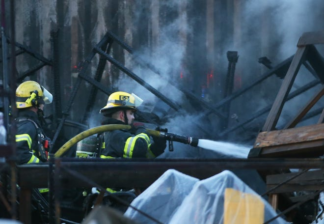 Eugene Springfield firefighters douse a fire in the lot of Mahindra Tractors in west Eugene on March 27, 2021.