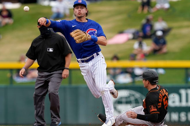 Chicago Cubs second baseman Nico Hoerner forces out San Francisco Giants' Mike Yastrzemski (5) as he turns a double play on Donovan Solano during the second inning of a spring training baseball game on Friday, March 26, 2021, in Mesa, Ariz.