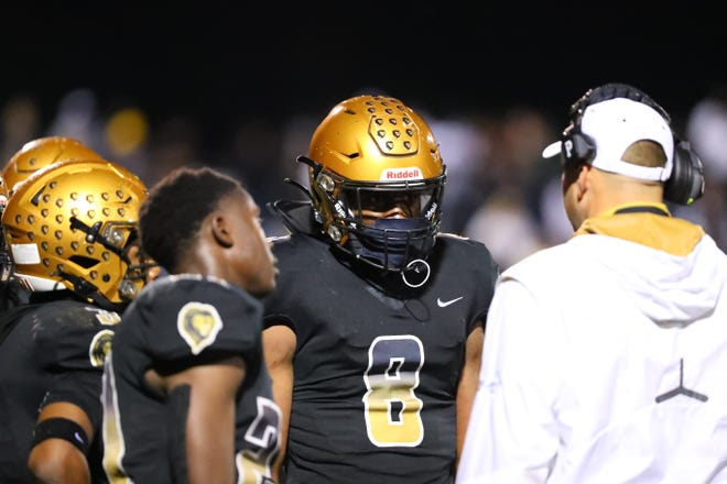 Shelby defensive lineman/linebacker Malaki Hamrick listens to instructions from Golden Lion coaches during their March 26, 2021 matchup against Kings Mountain.