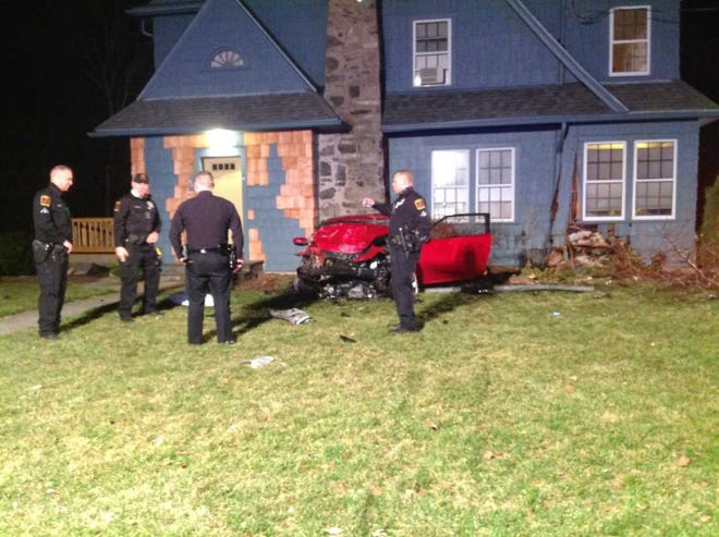 Police stand outside a home at 46 Rockwell St. in Norwich on Saturday where a car crashed into the house.