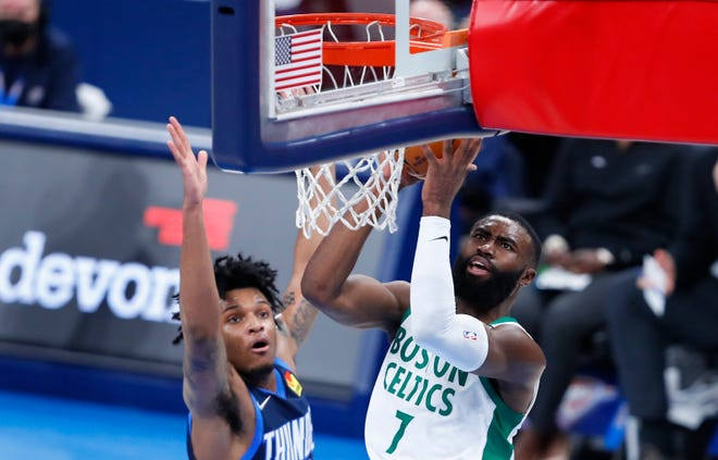 Celtics guard Jaylen Brown works to the basket for two as Thunder forward Josh Hall defends during the first half.
