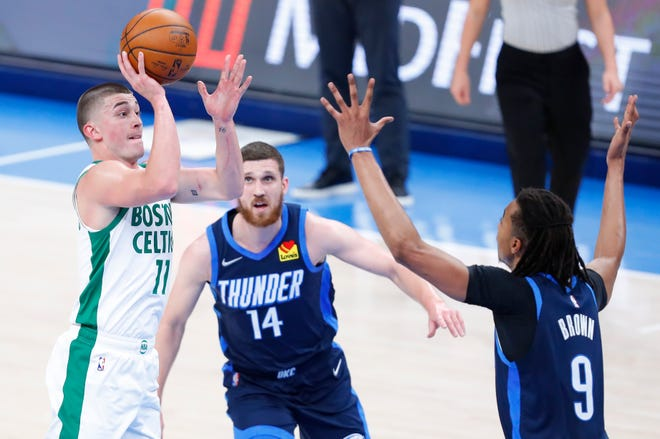 Celtics guard Payton Pritchard shoots as Thunder center Moses Brown (9) defends and guard Svi Mykhailiuk (14) looks on during the first half Saturday night in Oklahoma City.