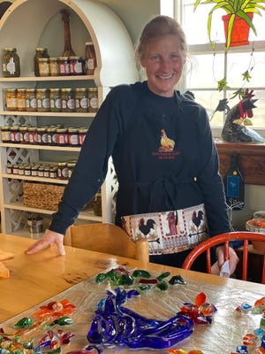 Jeannie Seabrook, owner of Glass Rooster Cannery & Old Hen Guest House in Sunbury, stands behind a piece of glass artwork that was created by her late sister, Susie Schmidhammer. The piece, featuring a glass rooster, will be hung in a building Schmidhammer had restored as her art shop, 1673 S. state Route 605 in Sunbury.