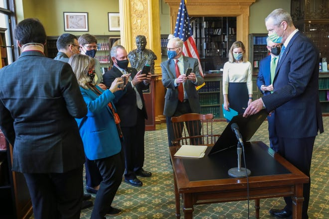 Senate President Karen Spilka, left, and lead negotiators Rep. Jeff Roy, left center, and Sen. Michael Barrett, center, snap pictures of the climate policy bill that Gov. Charlie Baker, right, had just signed into law in the State House library.