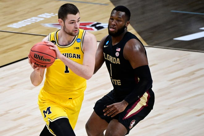 Michigan Wolverines center Hunter Dickinson (left) controls the ball against Florida State Seminoles forward RaiQuan Gray (right) in the first half during the Sweet 16 of the 2021 NCAA Tournament at Bankers Life Fieldhouse on March 28, 2021.
