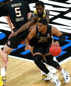 Florida State Seminoles guard M.J. Walker (23) moves past Michigan Wolverines guard Chaundee Brown (15) during the Sweet Sixteen round of the 2021 NCAA Tournament on Sunday, March 28, 2021, at Bankers Life Fieldhouse in Indianapolis, Ind.