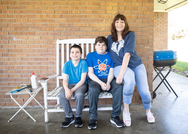 Kim Biers and her sons Chris Cdebaca, and David Cdebaca sit in shaded area of their driveway in Munford, Tenn on Friday, March 26, 2021. The single mother gets assistance from the free and reduced lunch program, but her money cards have been blocked and delayed by the state government.