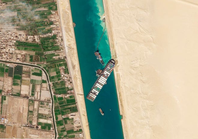 This satellite image from Planet Labs Inc. shows the cargo ship MV Ever Given stuck in the Suez Canal near Suez, Egypt, Sunday, March 28, 2021. Two additional tugboats sped Sunday to Egypt's Suez Canal to aid efforts to free a skyscraper-sized container ship wedged for days across the crucial waterway, even as major shippers increasingly divert their boats out of fear the vessel may take even longer to free. (Planet Labs Inc. via AP)