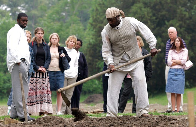 FILE- Historical interpreter Robert Watson, center, works a field as a group of visitors watches on the Great Hopes Plantation at Colonial Williamsburg in Williamsburg, Va., on May 19, 2005. Colonial Williamsburg is an immersive living-history museum where costumed interpreters of history reenact scenes and portray figures from that period. (AP Photo/Steve Helber, File)