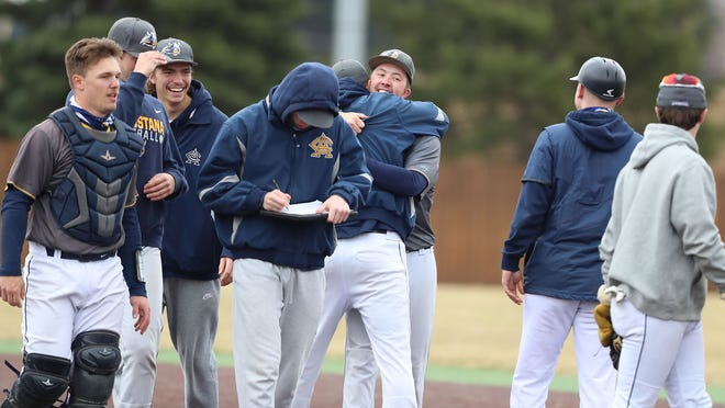 Augustana's Tanner Brown (center) receives congratulations from teammates after completing a perfect game against Minot State Saturday at Ronken Field at Karras Park.