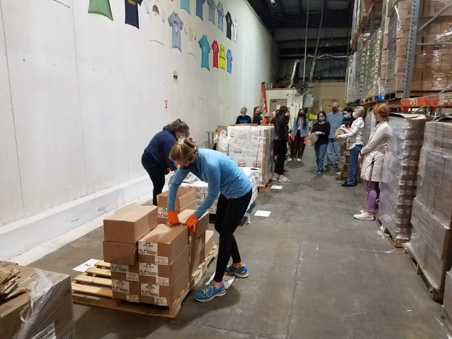 Volunteers sort food at the Second Harvest Operations Center. Second Harvest delivers food to 6 of Florida's top 10 most food insecure counties.