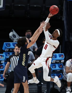 Arkansas Razorbacks guard Jalen Tate (11) shoots as Oral Roberts Golden Eagles guard Kareem Thompson (2) defends during the second half in the Sweet Sixteen of the 2021 NCAA Tournament at Bankers Life Fieldhouse.