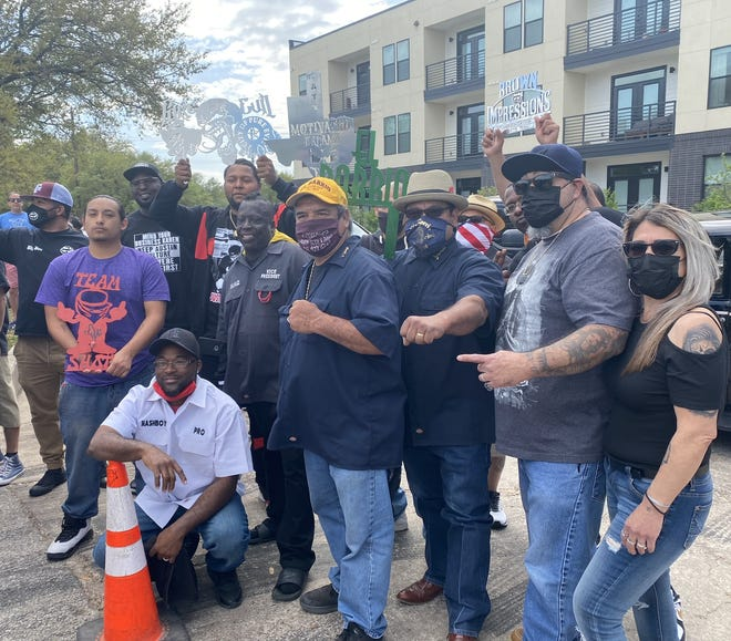 Members of low-rider car clubs pose at Sunday's rally at Edward Rendon Park in East Austin. Behind them are the Weaver apartments, where some tenants have complained about the noise at the weekly car shows.