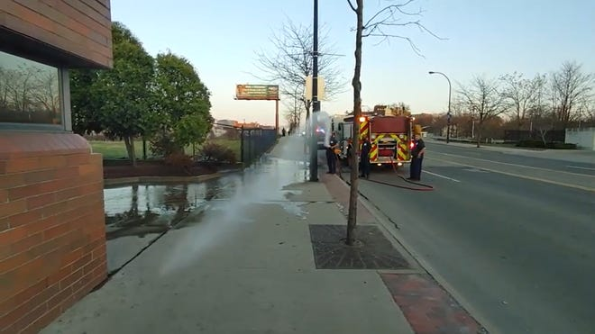 A screenshot of a video posted by Ryan Ohio Protests, which showed an activist filming a crime scene cleanup getting sprayed with a hose by an Akron firefighter.