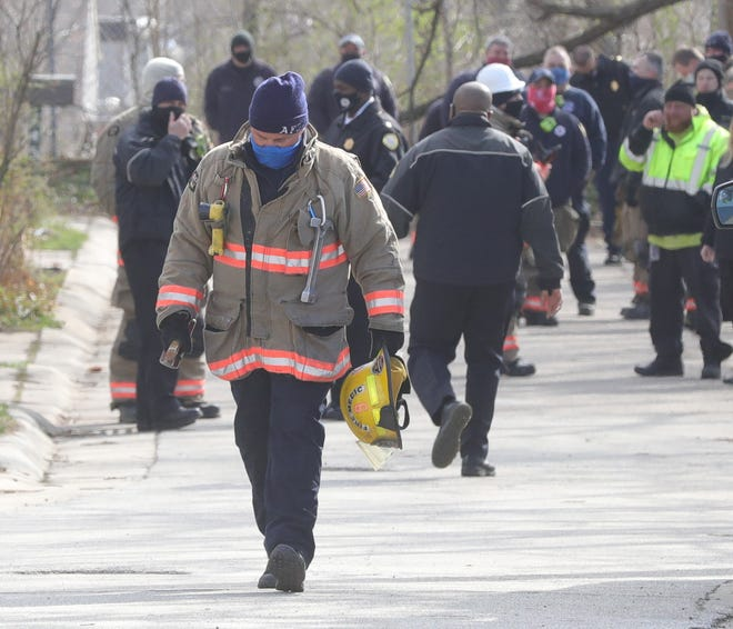 Police and fire investigators at the scene of a Moraine Avenue fire on Monday, March 29, 2021 in Akron, Ohio. [Phil Masturzo/ Beacon Journal]