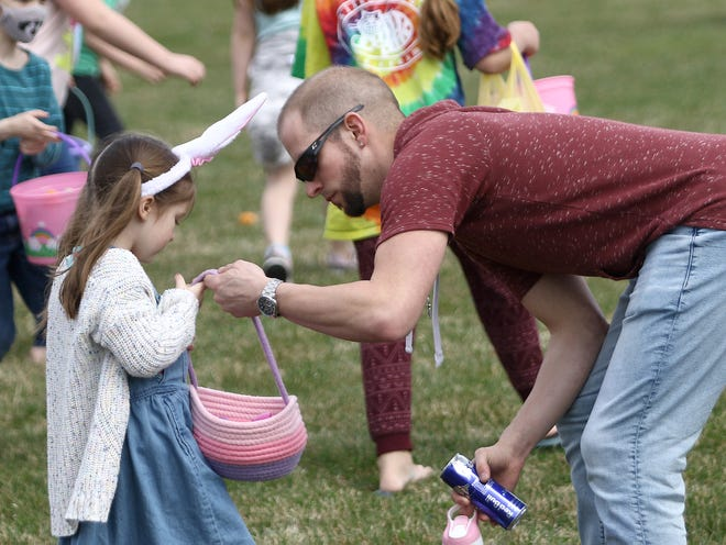 Tim Saunders, right, helps his daughter, Harlow, 5, during Saturday's Easter egg hunt at First Christian Church on West Beech Street.