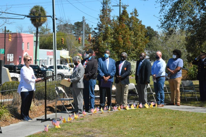 H.C. Emergency Management Director Susanne Peeples sings the National Anthem as county council officials look on during the Vietnam War Veterans Day Ceremony.