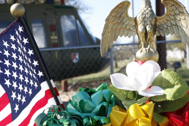 The Vietnam-era Huey helicopter is on display behind the the Vietnam War monuments and a wreath placed there for the Vietnam War observance Monday morning.