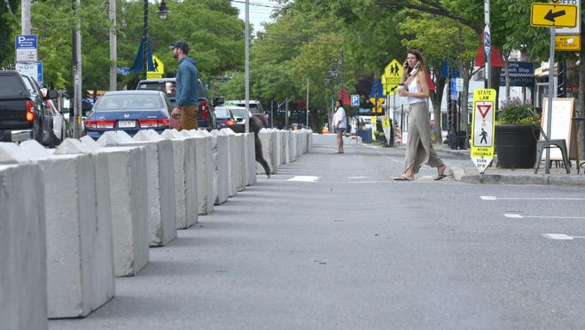 Pedestrians last summer had to get used to a new look as cement barricades diverted traffic down to one lane along Hyannis' Main Street. The barriers are expected to be installed again in mid-May, with some pattern changes to allow more parking. STEVE HEASLIP/CAPE COD TIMES