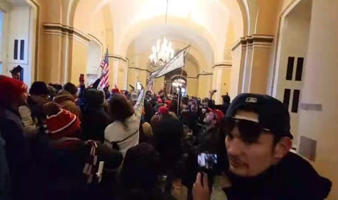 Investigators say this still image, filed as part of a criminal complaint in federal court shows Caleb Jones, of Columbus, among rioters at the U.S. Capitol on Jan. 6.