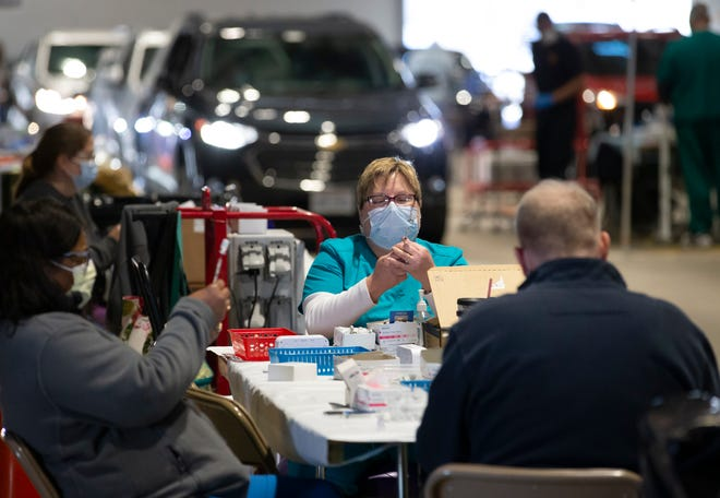 Columbus Public Health nurse Amy Haman fills doses of of the Pfizer-BioNTech COVID-19 vaccine at the drive-through vaccine clinic inside the Ohio State Fairgrounds in Columbus on Monday, March 29, 2021. All Ohioans over the age of 16 are eligible to get the vaccine as of Monday.