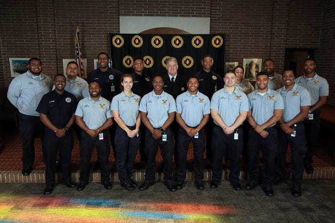 Columbus Fire Chief Jeffrey Happ, center, poses with the 17 cadets who graduated froma two-year program in which they earned certifications to prepare them for careers as firefighters orEmergency Medical Technicians.