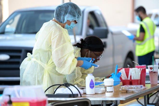 Health care workers conduct testing for COVID-19 at Lake Square Mall in Leesburg. [Cindy Peterson/Correspondent]
