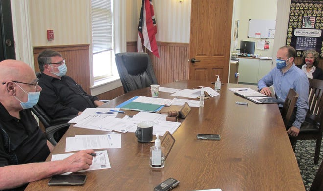Holmes County Economic Development Council Executive Director Mark Leininger, at right, discusses the enterprise zone program with commissioners Ray Eyler (from left) and Rob Ault, during Monday's meeting of the Holmes County Commissioners.