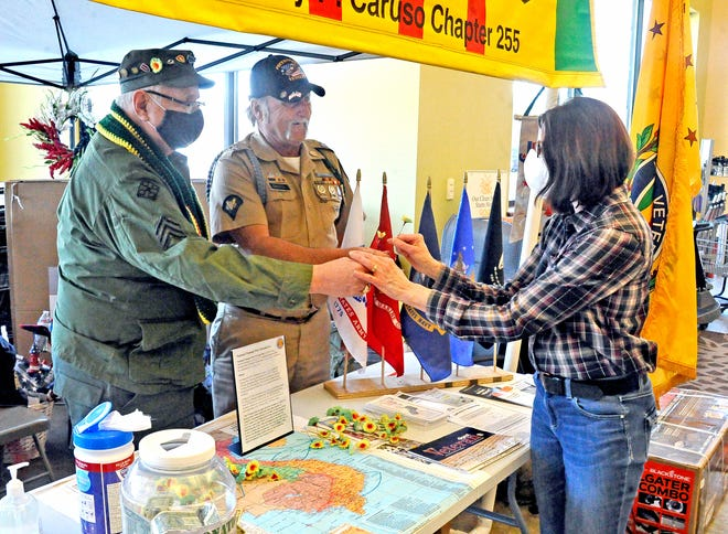 Dennis Amily and Jeff Sampsel, members of the Vietnam Veterans of America Barry Caruso Chapter, Wooster Ohio hand a poppy to Joyce Vura at Buehler's MIlltown in Wooster. Monday was National Vietnam Veterans Day and this is one way of remembering the soldiers who sacrificed during that time.