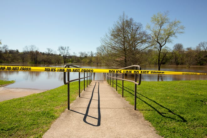 Police tape covers the entrance to a flooded portion of Riverwalk Park in Columbia, Tenn., on Monday, March 29, 2021.