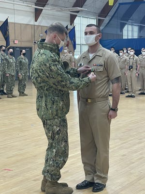 Capt. Mark C. Hazenberg, commanding officer of Officer Training Command Newport in Rhode Island, awards Tyler Zutell, a Jacksonville native and Officer Candidate School student, with the Navy and Marine Corps Achievement Medal on March 17.
