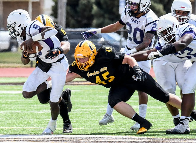 Garden City Community College defensive end Arvell Feruson (15) and linebacker Christian Fuhrman (45) meet at the quarterback and sack Arkansas Baptist's Cedric Andrews for a 10 yard loss Saturday at Broncbuster Stadium. The Broncbusters routed the Buffaloes in their season opener, 63-6.