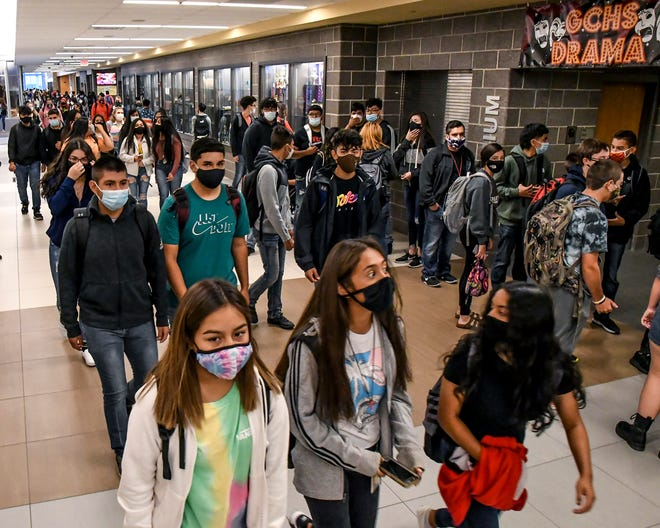 Garden City High School students make their way through the main hallway to their classes while wearing masks.