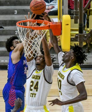 Garden City Community College's Mohamed Diarra, right, tips the ball into the basket as he and teammate Khadim Samb battle Hutchinson's Daniel Braster for a rebound March 6 during a game at Perryman Athletic Complex.