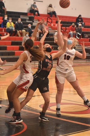 Chargers Hailey James, left, and Adah Swanson, right, battle a Stark County Rebel for a rebound in the varsity game on Saturday, March 6, in Orion.