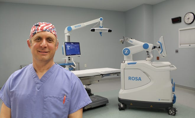 Dr. Mark Stewart, Orthopedic Surgeon with ORA Orthopedics, is shown with ROSA, the robot now available to assist in joint replacement surgeries at Hammond-Henry Hospital in Geneseo.
