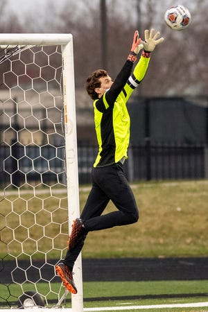 Galesburg goalie Kyler Smith goes up high for a save during the Silver Streaks' 3-0 loss to Quincy in WB6 Conference action on Wednesday, March 24, 2021 at Van Dyke Field.