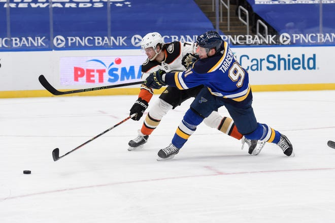 Anaheim Ducks' Ben Hutton (7) attempts to block a shot from St. Louis Blues' Vladimir Tarasenko (91) during the second period of an NHL hockey game on Sunday, March 28, 2021, in St. Louis.