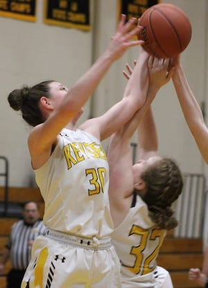 Keyser's Kaili Crowl (30) and Aly Smith (32) reach for the ball against Spring Mills.Smith scored 14 points to help lead Keyser in the loss, Crowl added four points.