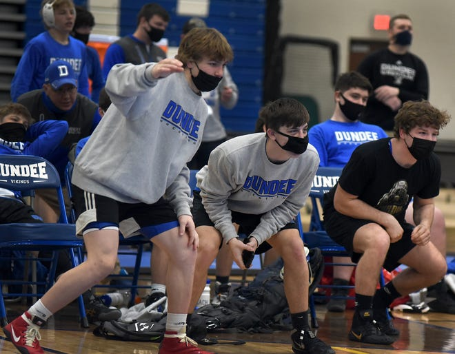 Casey Swiderski, Austin Fietz and Stoney Buell of Dundee cheer on their teammates during a match earlier this season. The Vikings will be bidding for their fourth straight Division 3 state title today in Kalamazoo.