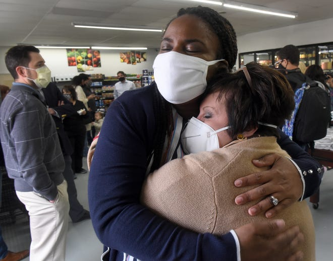 Pastor Heather Boone, founder of Oaks of Righteousness, receives a big hug from Monroe Public Schools Superintendent Julie Everly during the opening of The Village Market in Monroe.